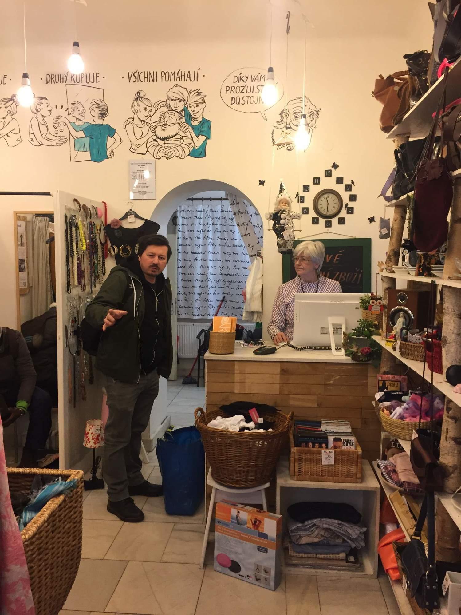 Dobrovolnice prodává v dobročinném obchodě Sue Ryder. Foto: Karolína Novotná