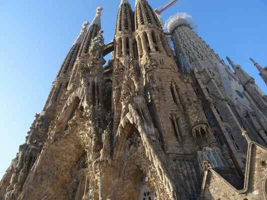 """Nejzajímavějším znakem těchto tří portálů jsou jejich okraje, které zblízka i zdálky vzbuzují dojem jakýchsi krápníků nebo organického kamene, stavba se tak jeví tvárnou, živou a tekutou. Také sochy v průčelí jakoby se """"vpíjely a utápěly"""" v proudu života, kterým tato fasáda kypí a přetéká. Tyto tekuté architektonické prvky jsou výsledkem Gaudího pracných technik. Gaudí nejprve namáčel shluky svázaných korálků do tekuté sádry a poté zkoumal, jak tyto části architektonicky včlenit do stavby samotné. Jde o jeden z mnoha unikátních a evolučních stavebních prvků celé baziliky a svědčí o výjimečném talentu a důvtipu tohoto architekta"""