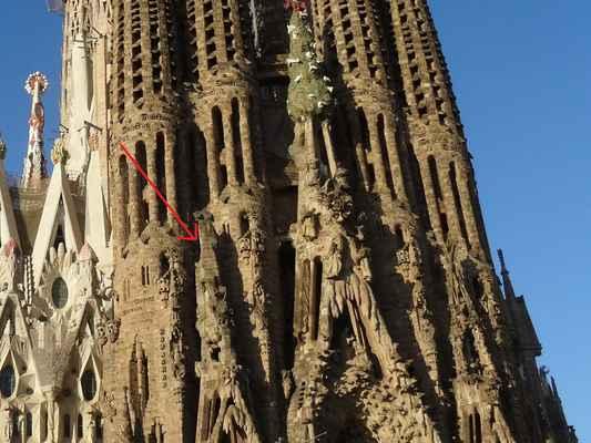 Šipka ukazuje na věž, která svým tvarem má symbolizovat horu Boží prst v pohoří Montserrat - viz odkaz  https://cs.wikipedia.org/wiki/Montserrat_(hora)#/media/Soubor:Cavall_Bernat.jpg