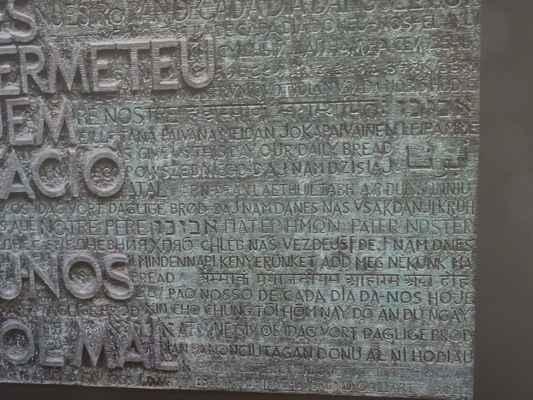 Dveře jižní fasády - Hlavní tématikou tohoto vstupu je text Otčenáše v katalánštině, který je tvořen velkými reliéfními písmeny a doplněn o vyryté modlitby ve 150 jazycích.