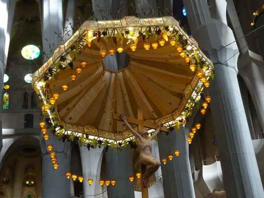 Monumentální baldachýn. Stejný Gaudí navrhl v roce 1912 pro katedrálu na Mallorce. Uprostřed vidíme sochu Ježíše na prostém dřevěném kříži, po okrajích baldachýnu pak visí obilí a vinné hrozny - symbol eucharistie. Kolem pak je umístěno padesát svítidel, jako odkaz na Lateránskou baziliku v Římě.
