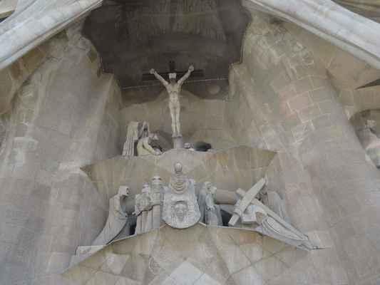 Pod Ukřižovaným Kristem vidíme sousoší. Zprava Kristus nesoucí kříž, uprostřed Veronika ukazuje roušku s otiskem Ježíšovy tváře, dvojice vojáků a zcela vlevo evangelista - portrét Antoni Gaudího.