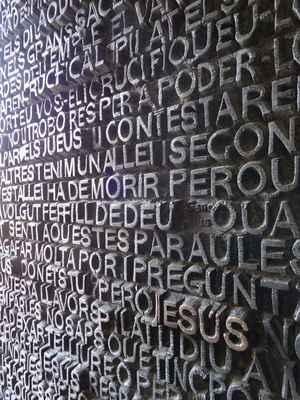 Dveře západní fasády s reliéfním písmem s úryvky z evangelií Matouše a Jana.