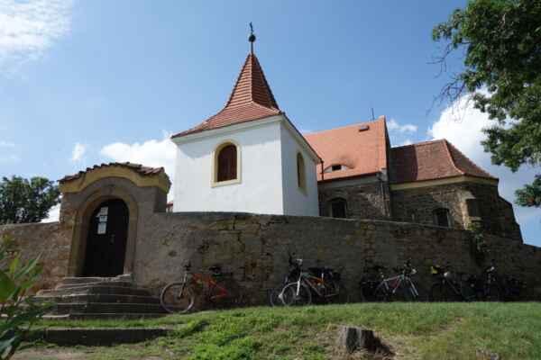 Kostel stojí na částečně uměle navršeném pahorku, kde původně stávala malá tvrz s kaplí zasvěcená sv. Markétě. Jádro kostela sv. Bartoloměje bylo vystavěno ve 13. století. Ve 14. století byla přistavěna loď kostela a presbytář. Poslední rekonstrukce proběhly v roce 1937. U kostela je hřbitovní brána, pocházející z roku 1777. Pozoruhodnou součástí kostelního areálu je zvonice. Ačkoli svým umístěním těsně u jižního boku kostela navozuje dojem běžné kostelní věže, jedná se ve skutečnosti o samostatnou zvonici, na kostel napojenou jen spojovacím krčkem.